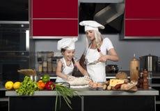 Het mamma onderwijst dochter aan kok Stock Foto's