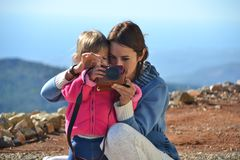 Het mamma onderwijst haar dochter aan het nemen van beelden stock foto