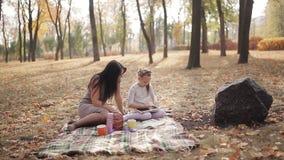 Het mamma onderwijst haar dochter om met krijt op een bordbrieven te schrijven, het alfabet Gelukkige familie in openlucht Moeder stock footage