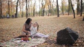 Het mamma onderwijst haar dochter om met krijt op een bordbrieven te schrijven, het alfabet Een jonge moeder heeft pret het spele stock videobeelden