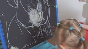 Het mamma onderwijst meisje om met krijt op een bord te trekken stock footage