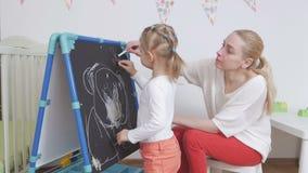 Het mamma onderwijst meisje om met krijt op een bord te trekken stock video