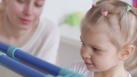 Het mamma onderwijst meisje om met krijt op een bord te trekken stock videobeelden