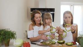 Het mamma onderwijst twee jonge geitjesdochters om bij de keukenlijst met ruwe groene paprika thuis in de keuken te koken moeder stock video