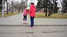 Het mamma onderwijst weinig dochter aan rolschaats in het park stock videobeelden