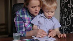 Het mamma onderwijst zoon om kleuren te schilderen stock footage