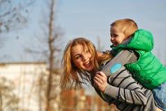 Het mamma rolt haar zoon op haar schouders piggyback royalty-vrije stock foto's