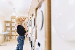 Het mamma toont haar dochter een wasmachine stock foto's