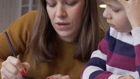 Het mamma toont haar leuke nieuwsgierige zoon hoe te om dieren correct te trekken stock videobeelden