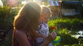 Het mamma toont het kind de bloem stock footage