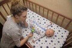 Het mamma toont rammelaar aan zijn pasgeboren kind, dat in een voederbak ligt stock fotografie