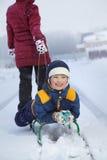 Het mamma trekt een slee met zijn zoon op sneeuwweg Stock Afbeeldingen
