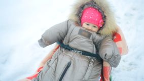 Het mamma trekt haar weinig baby op een slee in de winter stock video