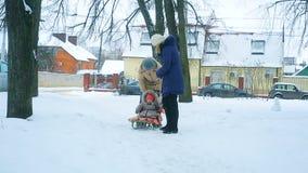 Het mamma trekt haar weinig baby op een slee in de winter stock footage
