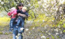 Het mamma van het de lentepark met tweelingen op plaid openlucht in appeltuin Stock Afbeelding