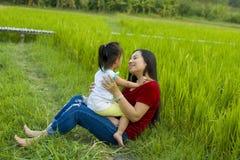 Het mamma van het levensstijlportret en dochter in geluk bij de buitenkant in de weide, Grappige Aziatische familie in een padiev royalty-vrije stock foto's