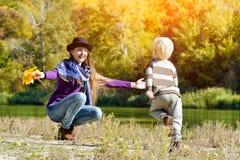 Het mamma vangt lopende zoon De herfst, een zonnige dag Rivierbank stock afbeeldingen