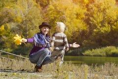 Het mamma vangt lopende zoon De herfst, een zonnige dag Rivierbank stock foto's