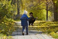 Het mamma vangt lopende zoon Herfst bos royalty-vrije stock foto's