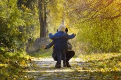 Het mamma vangt lopende zoon Herfst bos stock foto
