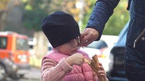 Het mamma veegt het gezicht van het kind met een sjaal na roomijs af stock footage