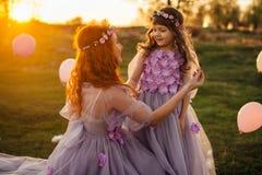 Het mamma verbetert haar dochter` s haar tijdens een gang bij zonsondergang Stock Foto's