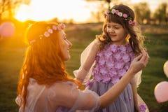 Het mamma verbetert haar dochter` s haar tijdens een gang bij zonsondergang Stock Fotografie