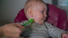 Het mamma verwijdert voedselschroot uit het kind stock video