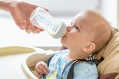 Het mamma voedt haar baby een fles melk Stock Foto