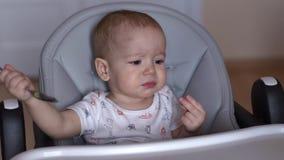 Het mamma voedt haar leuke baby met een lepel De kleine jongen eet kindhavermoutpap stock videobeelden