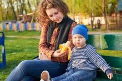 Het mamma voedt haar weinig zoon met een banaan op een bank in het park Gezond het Eten Concept royalty-vrije stock afbeeldingen