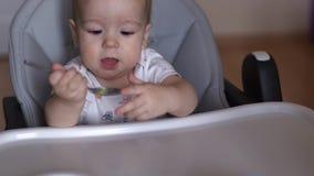 Het mamma voedt haar zoete baby met een lepel De baby neemt een lepel van zijn moeder stock videobeelden