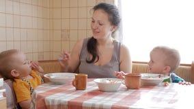Het mamma voedt twee zonen van de huishavermoutpap bij de lijst Één jongen zelf eet met een lepel Het tweede kind helpt een vrouw stock video