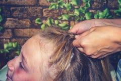 Het mamma weeft haar haar aan haar dochter, thuis maakt haar haar royalty-vrije stock afbeelding