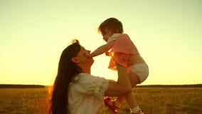 Het mamma werpt gelukkige dochter en kussen in zon, moederspelen een klein kind bij zonsondergang stock footage