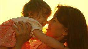Het mamma werpt gelukkige dochter en kussen in zon, moederspelen een klein kind bij zonsondergang stock videobeelden