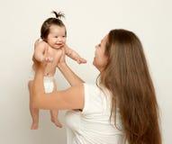Het mamma werpt op baby, spel en het hebben van pret, ouderschap, gelukkig familieconcept Stock Foto's