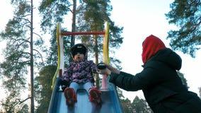 Het mamma zet op haar vuisthandschoenvuisthandschoen weinig dochter in een kleurrijk jasje dat op een multicolored dia in het de  stock video