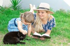 Het mammablonde in een hoed en haar dochter liggen op het gras en lezen een boek, gelukkige familie stock afbeelding