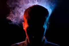 Het man gezicht is verborgen in de schaduwen op een terug geïsoleerde zwarte stock foto