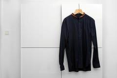 Het Man overhemd hangen op een hanger in garderobe Stock Foto