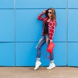 Het manier hipster meisje stelt in zonnebril met rode zak op de blauwe muur openlucht Royalty-vrije Stock Afbeelding