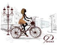 Het maniermeisje berijdt een fiets, met een muzikale staaf wordt verfraaid die Stock Foto's