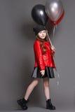 Het maniermeisje met kleurenballons knipoogt Studiofoto op een donkere achtergrond Stock Foto