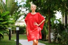 Het manierportret van jonge schoonheidsvrouw in het rode kleding stellen overtreft royalty-vrije stock afbeelding