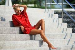 Het manierportret van jonge schoonheidsvrouw in het rode kleding stellen overtreft Stock Afbeelding