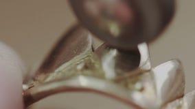 Het mannelijk de hand oppoetsen en polijsten van de juwelenmaker een gouden ring van gevormde kroon in juwelen die workshop maken stock video