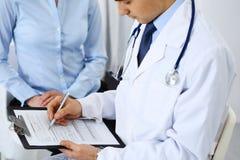 Het mannelijke aanvraagformulier van de artsenholding terwijl het raadplegen van vrouwelijke patiënt in het ziekenhuis Geneeskund stock foto