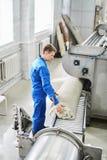 Het mannelijke arbeider schoonmaken krijgt tapijt van een automatische wasmachine en draagt het in de klerendroger royalty-vrije stock afbeelding