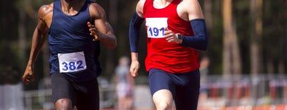 Het mannelijke atleten sprinten Twee die mensen in sportkleren bij de renbaan in professioneel stadion in werking worden gesteld stock afbeelding